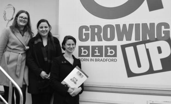 "Three people stood in front of sign with text ""Growing Up"" and the Born in Bradford logo"